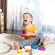 Stock Photo: Funny child playing with color toy indoor