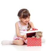 Happy child girl holding gift box with kitten — Stock Photo