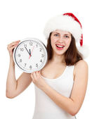 Cute girl in Christmas red santa hat with clock over a white bac — Stock Photo