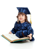 Little girl kid in academician clothes with book — Stock Photo