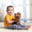 Kid hugging puppy indoor — Stock Photo