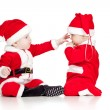 Stock Photo: Two funny small kids in Santa Claus clothes isolated on white ba