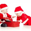 Two funny small kids in Santa Claus clothes with gift box — Stock Photo