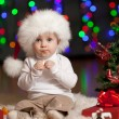 Funny baby in Santa Claus hat on bright festive background — Stock Photo #12084844