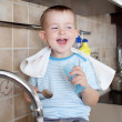 Funny little child boy washing dish on kitchen — Stock Photo
