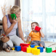 Foto Stock: Mother and kid boy role-playing together indoor