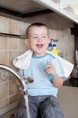 Funny little child boy washing dish on kitchen — Stock Photo