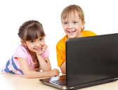 Happy children boy and girl using a laptop — Stock Photo