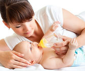 Young mother feeding her adorable baby — Stock Photo