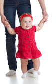 Little baby girl doing first step with help of mother — Stock Photo