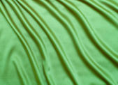 Green satin or silk fabric background — Stock Photo