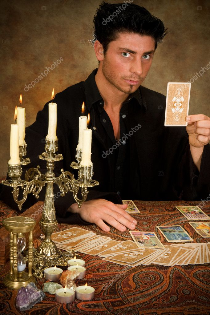 Halloween scene of a young fortune-teller holding a tarot card  Stock Photo #12361147