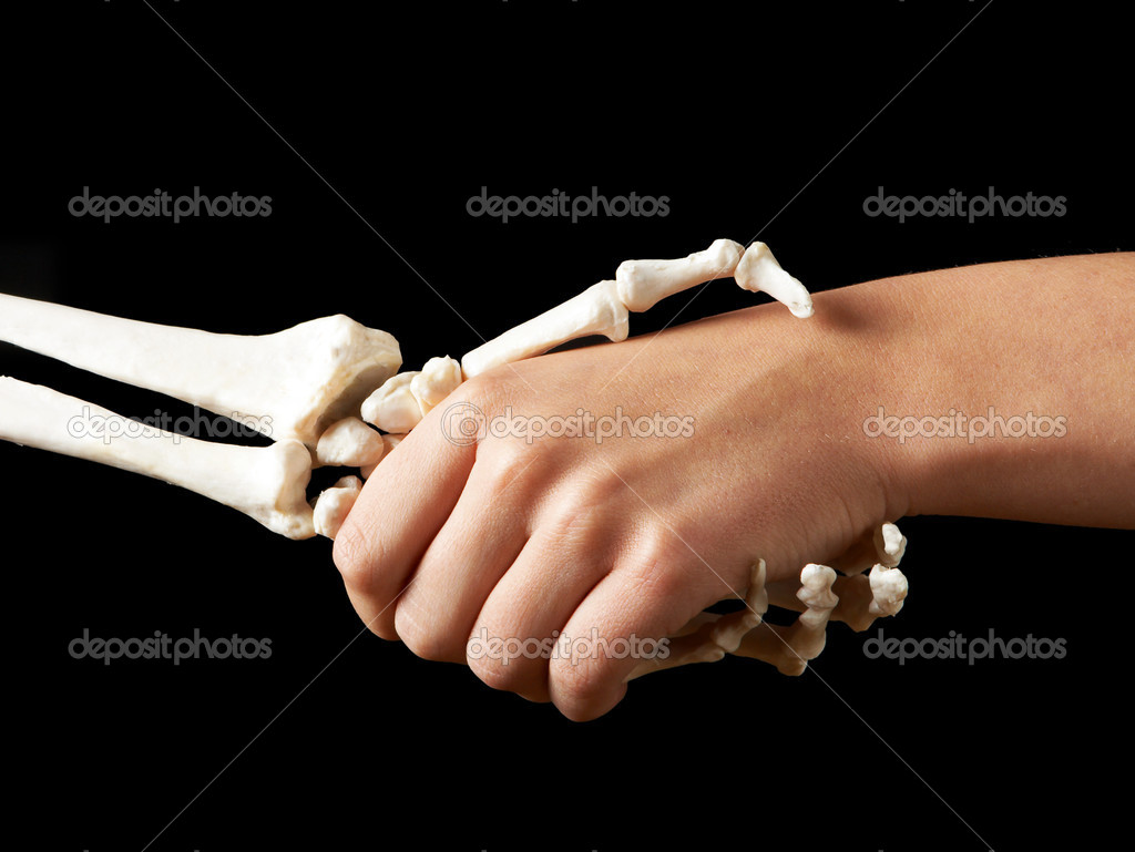 Female hand shaking hands with a skeleton hand  Stock Photo #12361481