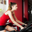 Stock Photo: Young womexercising at gym