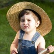 Royalty-Free Stock Photo: Boy with straw hat, a young outfielder playing with a hose