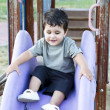 Cute baby playing on sliding board, smiling — Stock Photo #11303367
