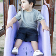 Caucasibaby boy playing on sliding board — Stock Photo #11303373
