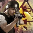 Stock Photo: Paintball player on graffiti background with intense orange ligh