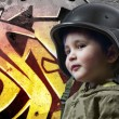 Baby playing war with military helmet against graffiti backgroun — Stock Photo #11303397