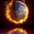 A global warming concept. Planet Earth burning over water reflec — Stock Photo
