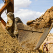 Excavator digging a deep trench, working, sand - Stock Photo