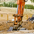 Stock Photo: Loader Excavator standing in sandpit with risen bucket over clou