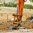 Loader Excavator standing in sandpit with risen bucket over clou - Stock Photo