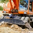 Orange excavator on a road - Stock Photo
