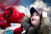 An adorable baby boy over a red planeputting his hands to his he — Stock Photo