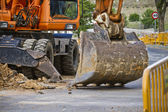 Closeup skid steer loader excavator at road construction work — Stock Photo