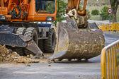 Closeup skid steer loader excavator at road construction work — Stock Photo