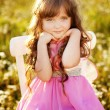 Cute child girl at camomile field - Stockfoto