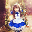 Alice girl in a fairy country is riding on a swing in a garden — Stock Photo