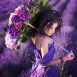 Stock Photo: Beautiful girl in a field of lavender with an umbrella of flowers