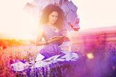Mooi meisje in het lavendel veld op een troon van boeken — Stockfoto