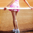 Royalty-Free Stock Photo: Legs of young girl in a closed tennis court with ball and racket