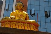 A statue of Buddha in front of the modern building in Kathmandu, Nepal — Stock Photo