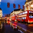 Royalty-Free Stock Photo: Red Bus on the Rainy Street of London in the Night, United Kingd