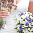 Bride holds in hand glass of champagne and wedding bouquet — Stock Photo