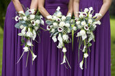 Three bridesmaids holding wedding bouquets — Stock Photo