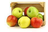 Assorted fresh apples in a wooden crate — Stock Photo