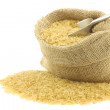 Unpolished rice (whole grain) in a burlap bag — Stock Photo