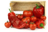 Rote paprika und tomaten in einer holzkiste — Stockfoto