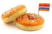 Orange donuts with red,white and blue sprinkles and flag toothpicks — Stock Photo