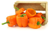 Fresh orange bell peppers in a wooden crate — Stock Photo
