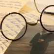 Old pair of glasses on some letters — Stock Photo #11832609