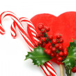 Stock Photo: Christmas candy canes with branch of holly on red hart