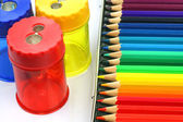 A box of coloring pencils and some pencil sharpeners — Stock Photo