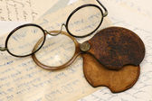 A pair of spectacles and a magnifying glass — Stock Photo