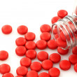 Red pills coming from a bottle — Stock Photo #11870983
